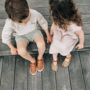 boys tan leather sneakers and girl wearing espadrille sandals