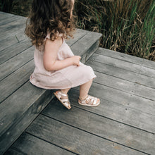toddler girl wearing rose gold sandals and pink dress