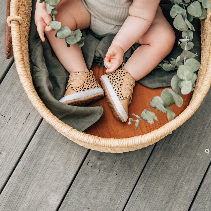 baby in a basket wearing prewalker boots