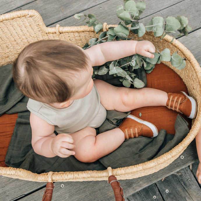 baby boy in basket wearing tan leather prewalker baby boots