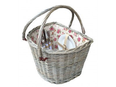 A wicker picnic basket for the front of a bicycle, with a floral lining and a pair of carrying handles. There are cutlery and crockery in the basket.