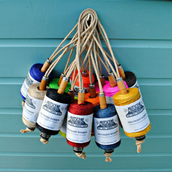 11 old wooden bobbins hanging up with all sorts of different coloured spools of twine on them.