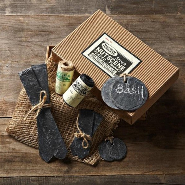 A cardboard gift box with slate plant labels, two spools of twine and hessian sacks.