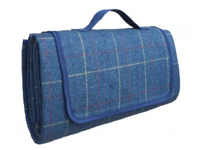 A pale blue, tweed picnic blanket folded up with a carrying handle at the top.