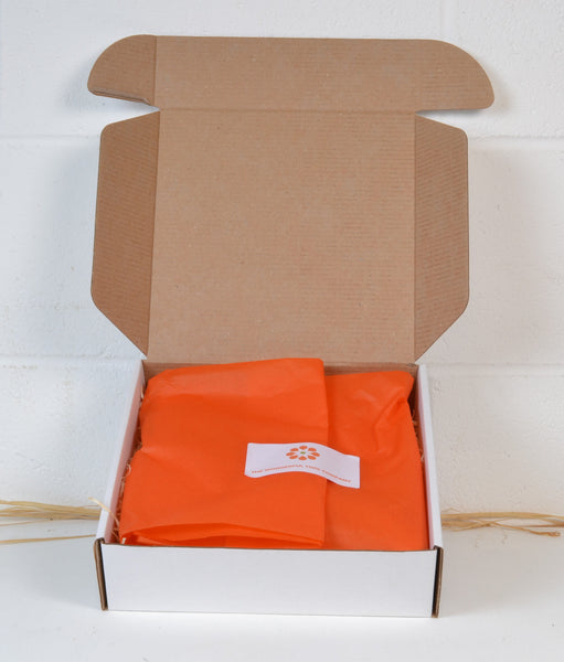 A white cardboard box with orange tissue paper inside to show how the trowel would be despatched.