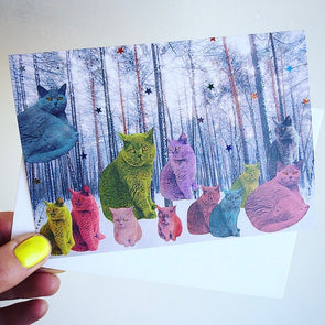 Holding pastel cats in forest card