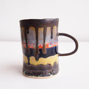 Handmade ceramic coffee mug with stripes and runny glaze