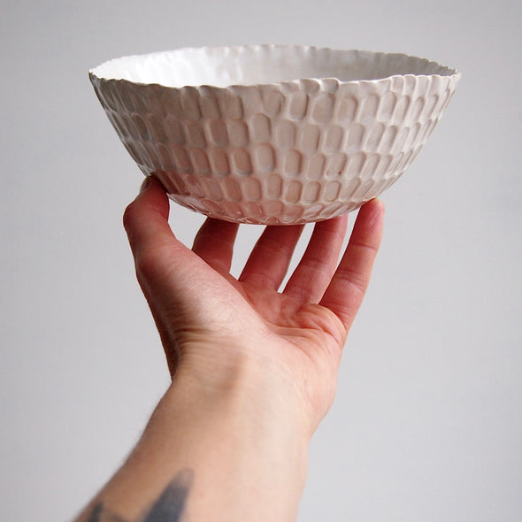 Holding a textural white serving bowl