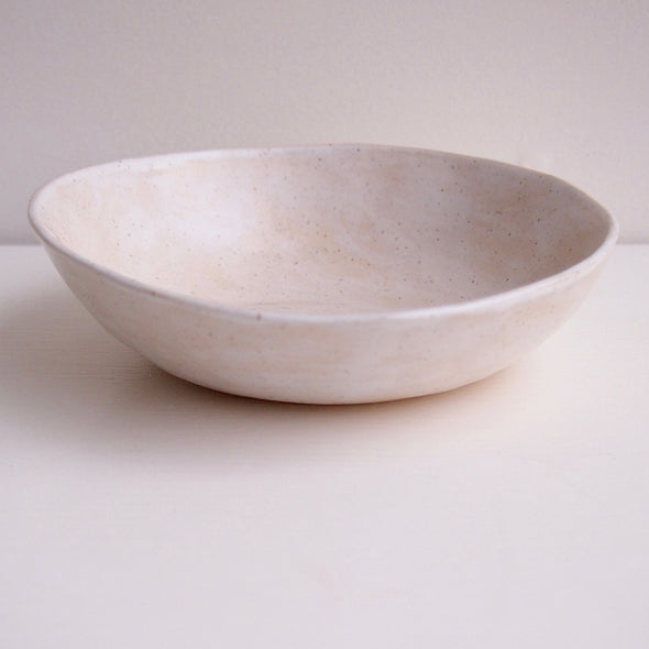 Side of cream speckled pottery cereal bowl