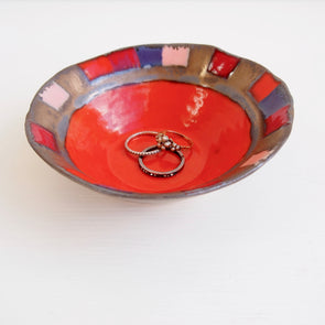Orange ceramic ring dish with pink, red and purple squares and gold detail.