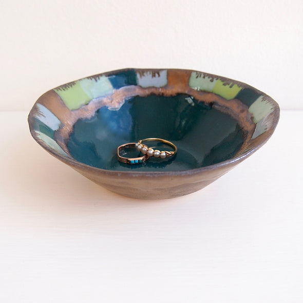 Teal ceramic ring dish with squares and gold detail.