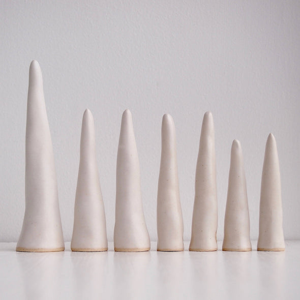 Row of Satin white pottery ring cones
