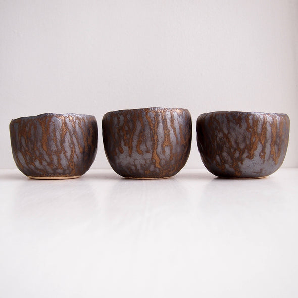 Row of teal and gold pottery ring bowls