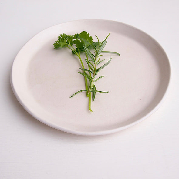 White satin pottery plate with herbs
