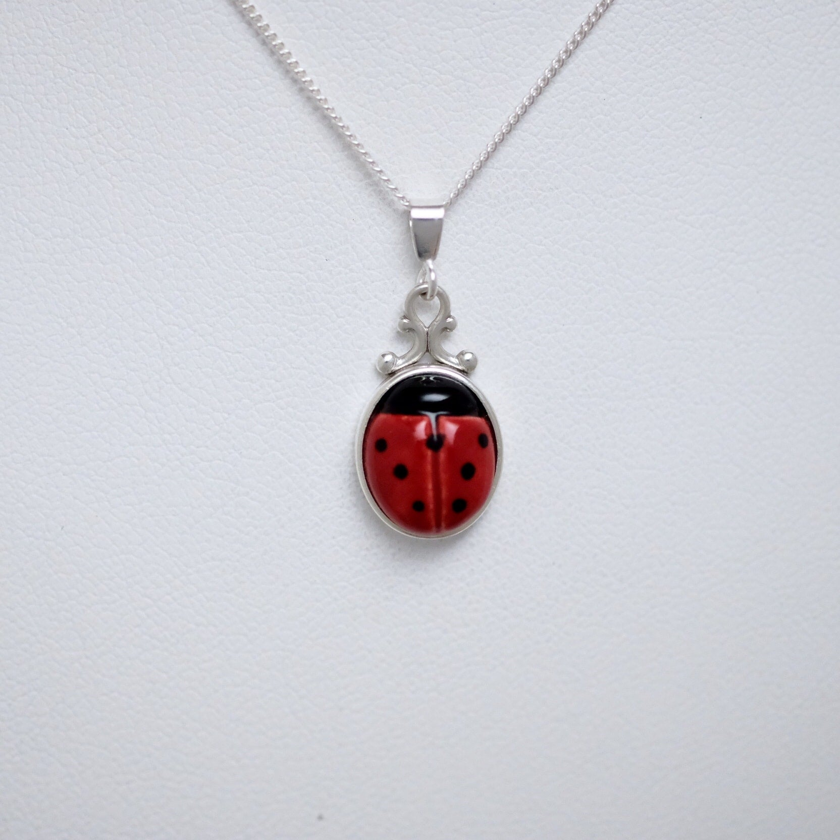 Porcelain ladybug with silver base (small pendant) by Joseph Chiang