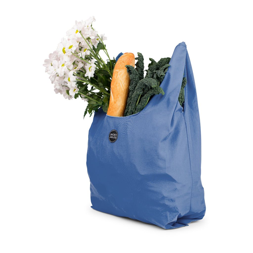 Individual marine blue reusable market shopping bag filled with groceries
