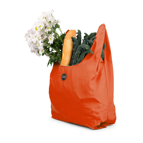 Single reusable market bag in sunset orange filled with shopping