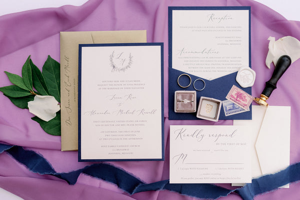 navy and gold pocket invitation with calligraphy and monogram crest