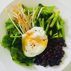 Green bowl with black beans and poached egg