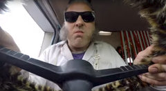 David Walliams driving with leopard print fuzzy steering wheel cover for TV Movie RatBurger