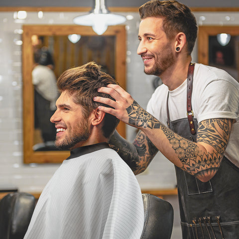 tattooed hairdresser cutting mans hair while wearing a neocape