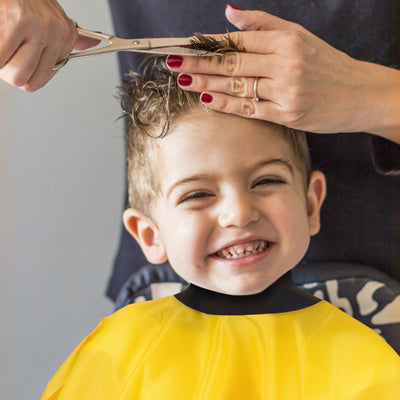 smiling boy having haircut whilst wearing a neocape yellow childs gown