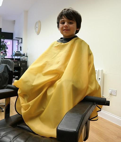 child sitting in salon chair wearing yellow childs neocape gown