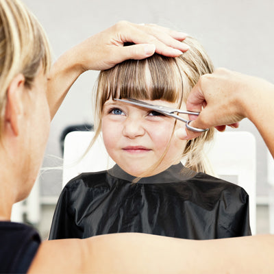 girl having fringe cut in black neocape childs gown