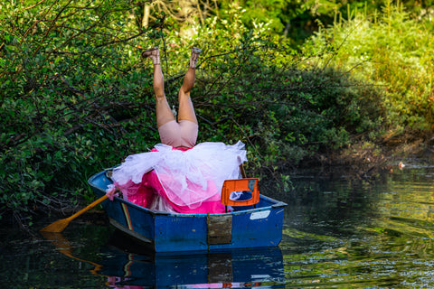 Person wearing pink dress standing upside down in a wooden rowboat butt joke