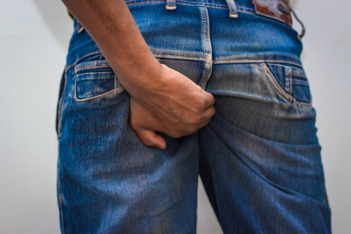 Man holding onto his butt with discomfort from an anal yeast infection