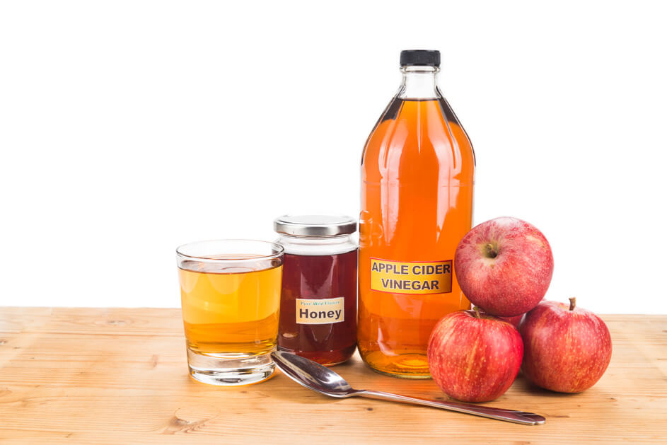 Bottle of apple cider vinegar with  honey, apples and a glass with spoon