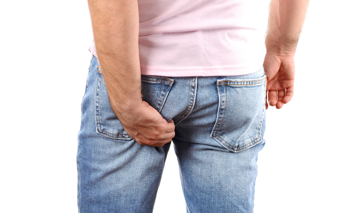Man itchy his butthole through his jeans