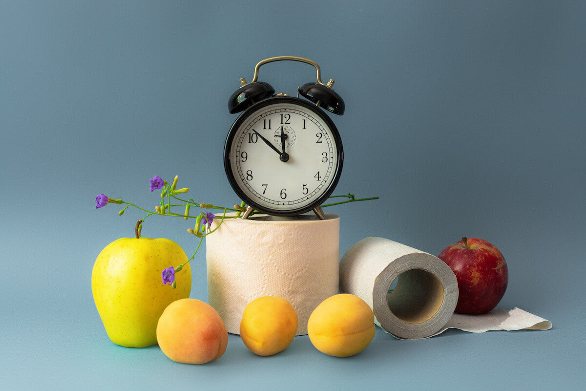 Foods surrounded a roll of toilet paper and alarm clock to suggest going to the bathroom