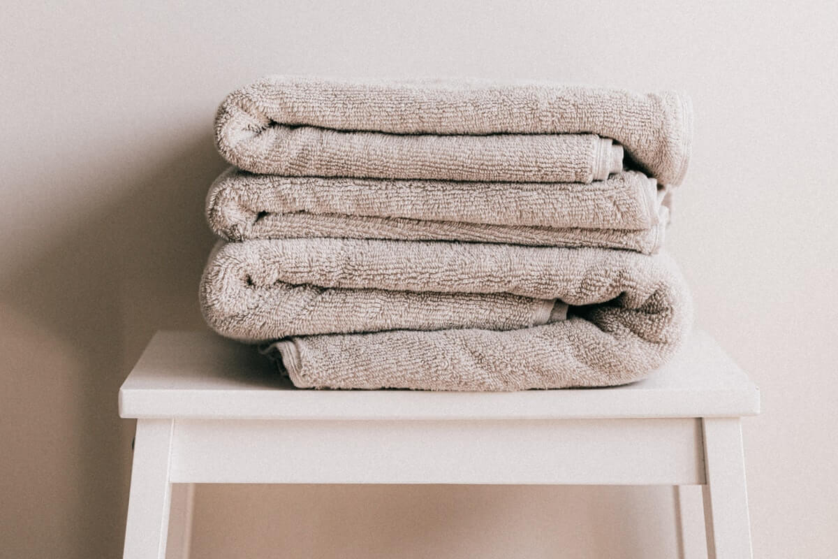 Spa towels stacked on a stool
