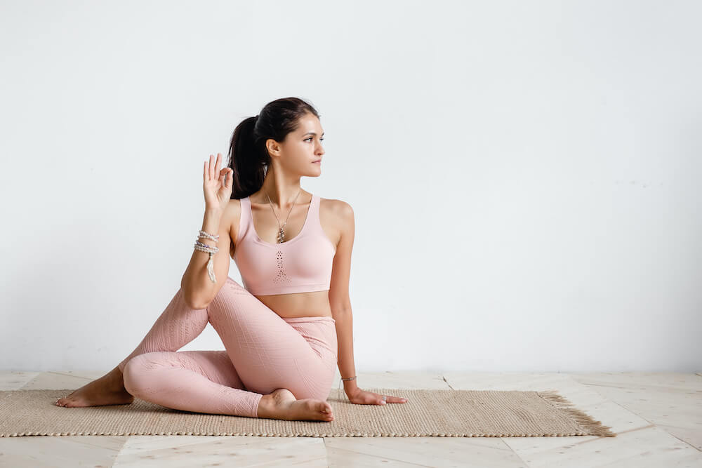 Woman in half spinal twist pose.