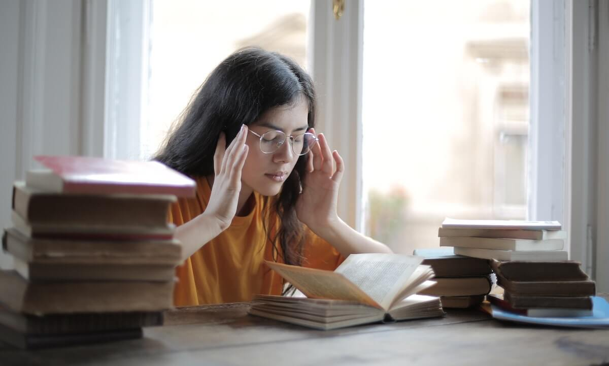 Woman sitting a desk with books, looking stressed