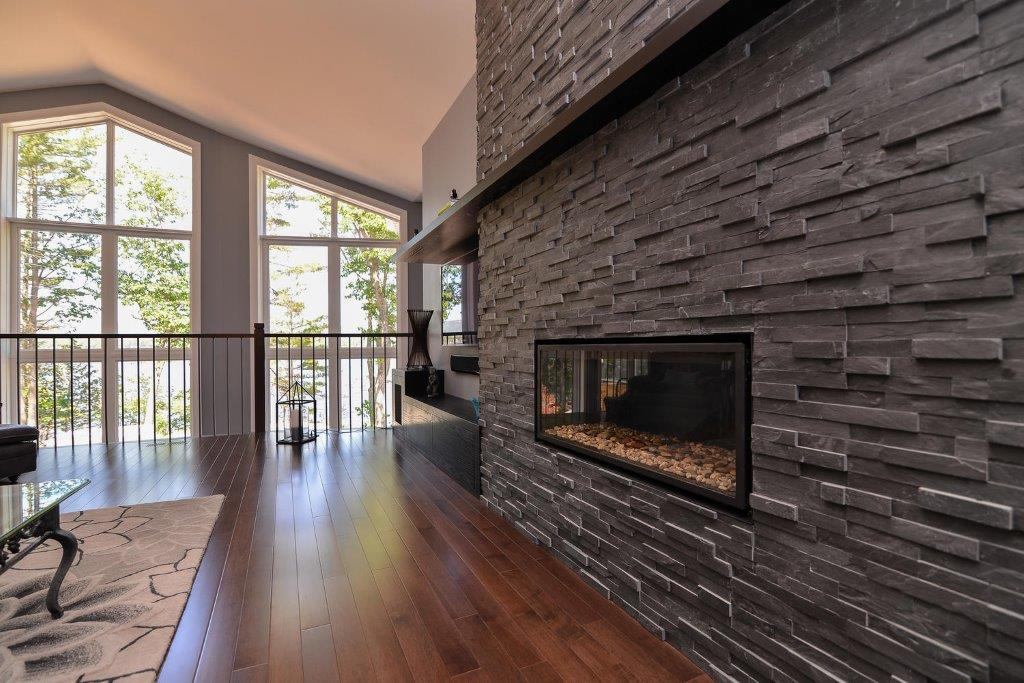 Stone Fireplace with a Dark Maple Floor