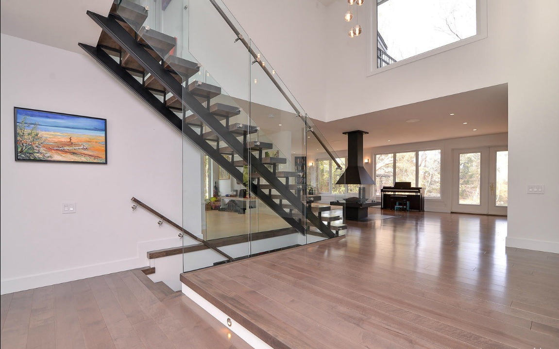 glass stairs and grey hardwood flooring