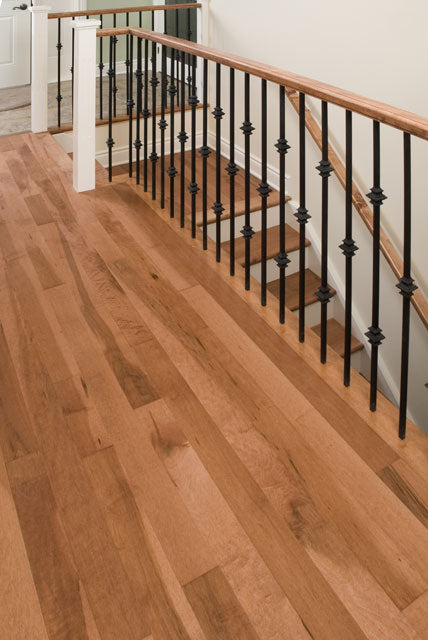medium toned wood flooring with a custom stair case