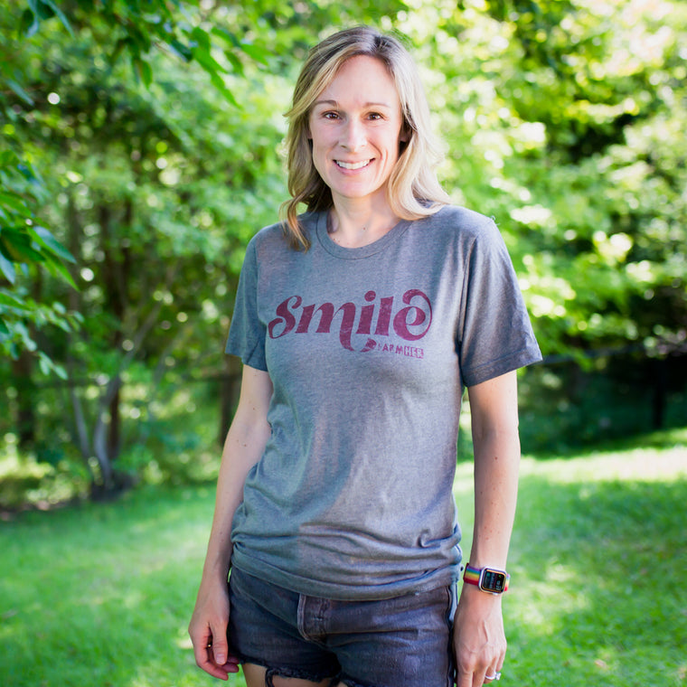 "Smile like it is going out of style and spread the love around to your friends and neighbors. This super comfy cotton blend T-Shirt features the word ""Smile"" and the FarmHer logo.  Unisize Fit  Non-fitted style. See sizing chart.  Model is wearing a small."