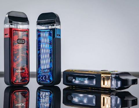 Red, blue, and gold SMOK Nord X vape devices lay atop a mirrored backdrop.