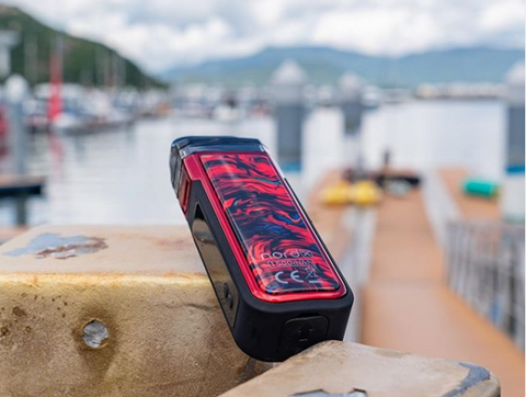 A red Nord X vape system sits on a pier with boats and water in the background.