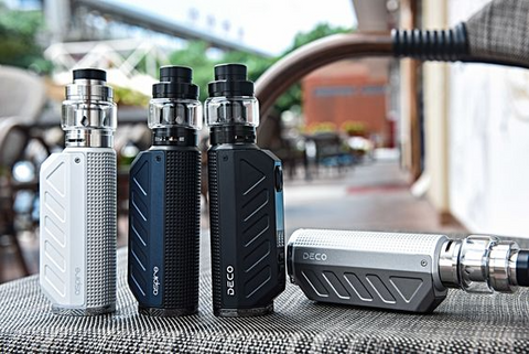 Four Aspire Deco kit vape devices placed on a park bench in an urban setting.