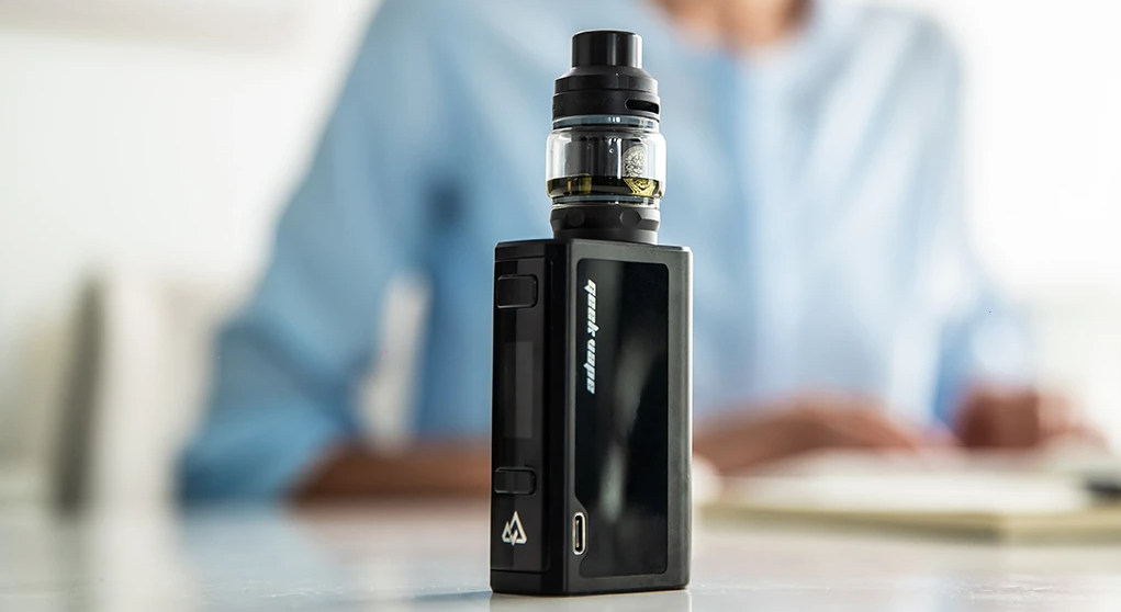 A Geekvape Obelisk with a woman in the background.