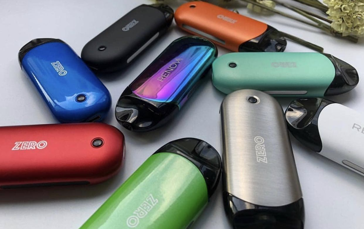 Several colorful Vaporesso vapes scattered atop a surface.