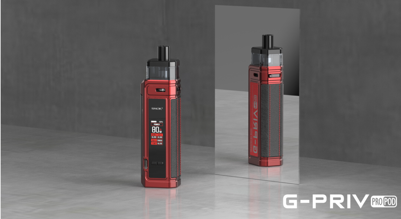A red vape displayed on a grey surface in front of a mirror.