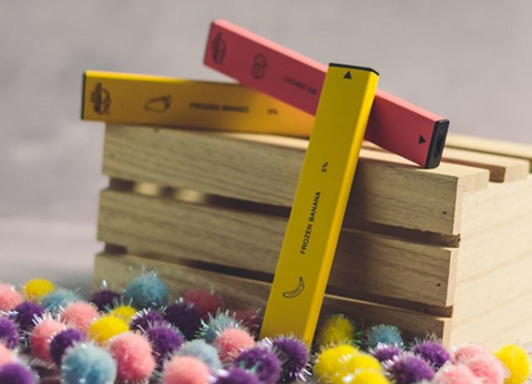 Three disposable vapes laying atop a wooden crate with colorful balls surrounding them.