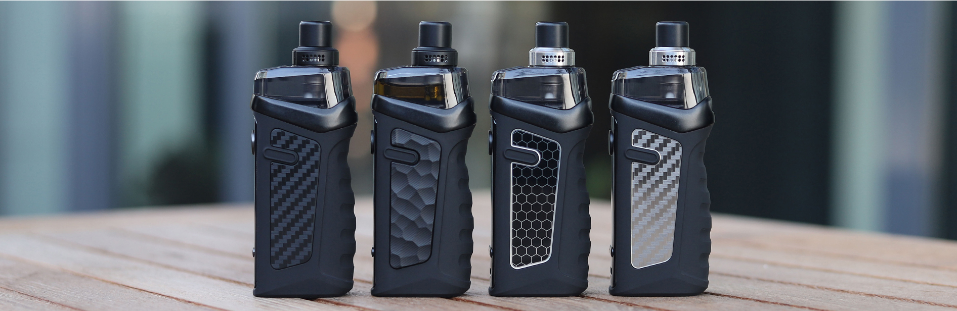 Four Vandy Vape pod devices sitting on a surface outside.