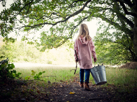 child walking away from the camera, into the woods with a steel bucket. Facing away.