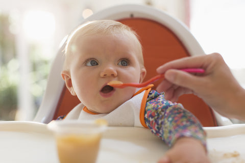 Baby in high chair eating baby food.